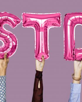 Hands holding STD word in balloon letters