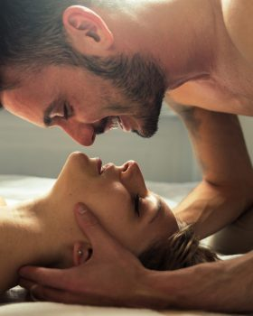 Image of couple in love have a romantic kiss on the bed at home.