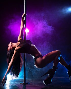 Young sexy slim brunette woman pole dancing in dark interior with smoke and lights