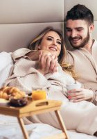 Young happy couple having breakfast in luxury hotel room, watching TV.