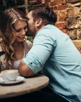 Smiling couple at a coffee shop spending time together. Man whispering in the ears of his girlfriend sitting in a restaurant.