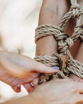 Woman bound with a rope in Japanese technique shibari at the tropical river